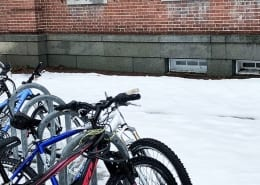 Student's bikes on a snowy campus day.