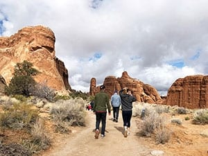 Family walking through the red rocks of Moab.
