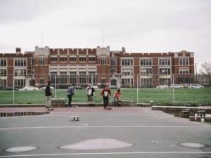 teen-boys-skateboard-outside-school